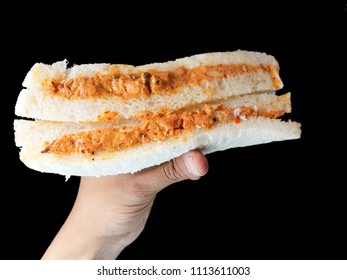 hand holding an isolated chicken tikka sandwich with mayonese in black background