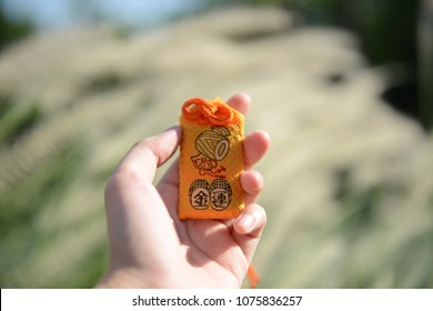 A hand holding Japanese amulet (Japanese on the amulet is mean wealthy   )