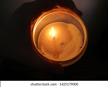 hand holding a jar candle lit with a flame in a dark room close up