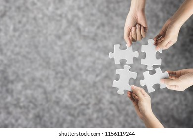 Hand holding jigsaw puzzle with copy space for teamwork concept.