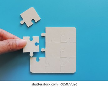 Hand holding a jigsaw puzzle piece connection on blue background.