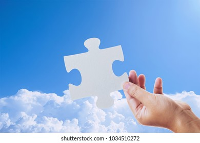 hand holding a jigsaw puzzle and sky background