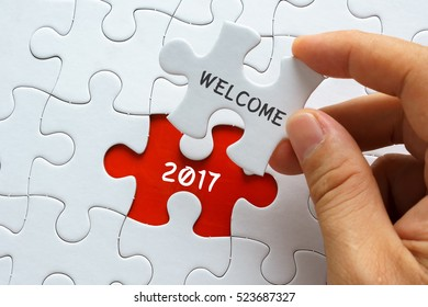 Hand holding jigsaw puzzle with word WELCOME 2017.