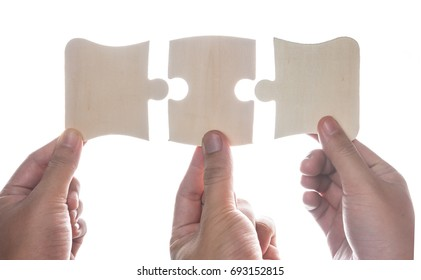 Hand holding jigsaw puzzles isolated over white,wooden puzzle.