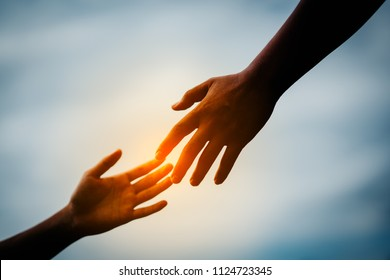 Hand to hand holding jointed connect for team on dark light center background. Hand of kid or child and parent or mother show love relationship teamwork together