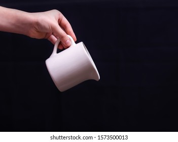 hand holding a jug on a dark background