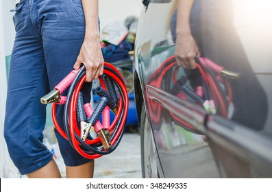 Hand holding jumper cable for recharge the battery car