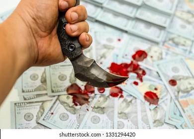 Hand holding karambit knife on stack bundles of 100 US dollars banknotes bloody