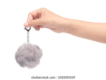 hand holding keychain Grey Fur ball isolated on white background