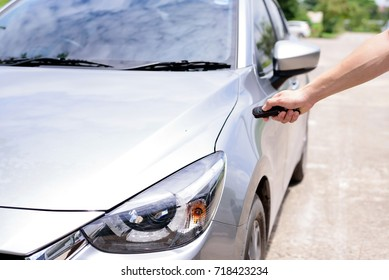 Hand holding a keys and pushing remote control for open new car.