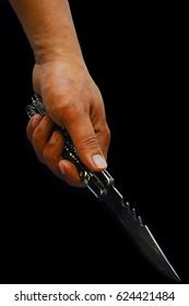 hand holding knife over black background