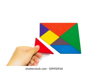 hand holding the last piece to complete a square tangram puzzle colorful wooden puzzle for kid on white background