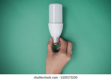 Hand holding LED Bulb with Lighting on green sky background. Eco power concept.