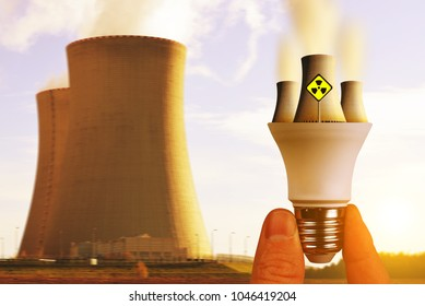 Hand holding LED light bulb with nuclear power plant at sunset.Atomic energy concept.