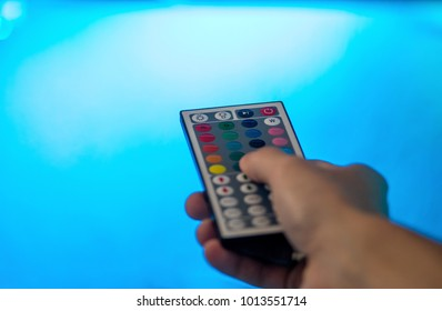 Hand holding a LED light remote control, changing light brightness, with a blue background from the LED illumination