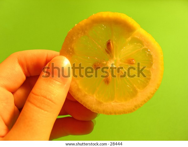 hand holding a lemon slice next to a vibrant green background.