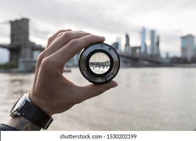 Hand, die eine Linse hält gegen die Skyline von New York City