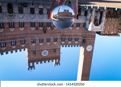 Hand holding a lens ball with refraction of Campo Square (Piazza del Campo) and town hall building (Palazzo Comunale) agaist blue sky.  Italy