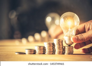 Hand holding a light bulb with coins stack. Creative ideas for saving money concept. Money management for the future