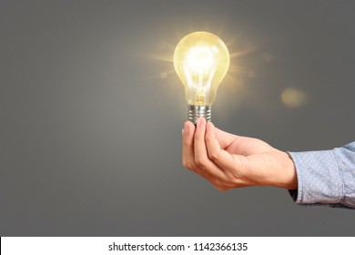 hand holding a light bulb with energy