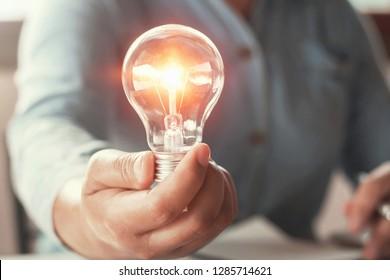 hand holding light bulb energy power concept