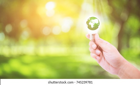 Hand holding a light bulb with energy green world inside on nature background, environment and ecology concept .