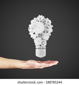 hand holding light bulb and gears