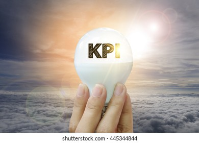 hand holding light bulb with KPI  text on sky background , business concept , business idea , strategy concept
