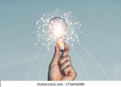 A hand holding a light bulb Lifted up in the sky outdoors With the idea of ​​creating new ideas And creativity and inspiration in imagination