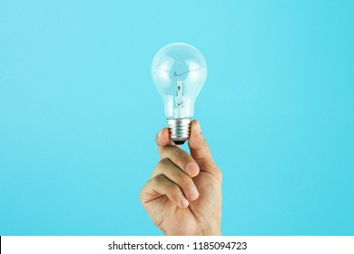 Hand holding light bulb on blue background. Concept for new ideas with innovation and creativity.