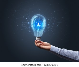 Hand holding light bulb on dark background. Networking idea concept
