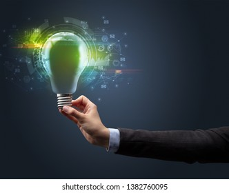 Hand holding light bulb on dark background. New business idea concept