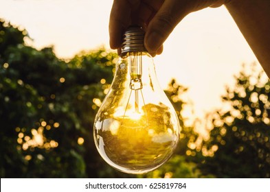 hand holding a light bulb with sunset power concept power the future