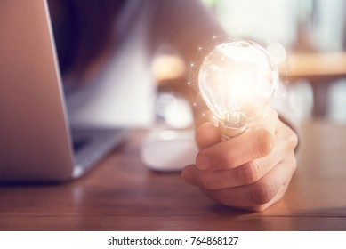 Hand holding light bulb while using on laptop, New ideas and creativity concept.