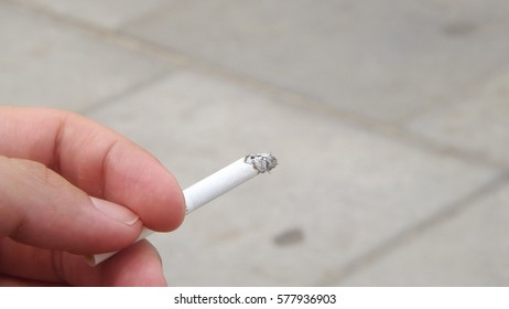 Hand holding a lit cigarette