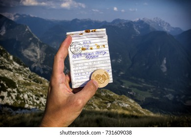 Hand is holding a logbook and Czech Wooden Geocoin in Julian Alps, Slovenia.