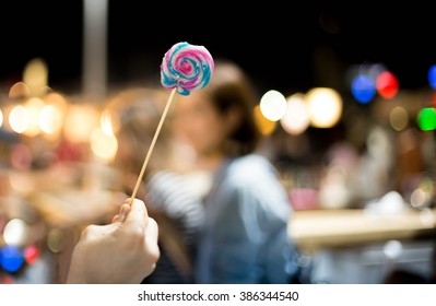 Hand holding loli pop candy with bokeh light and people in  background