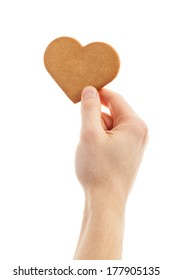 hand is holding a love shaped gingerbread cookie. Isolated on white.