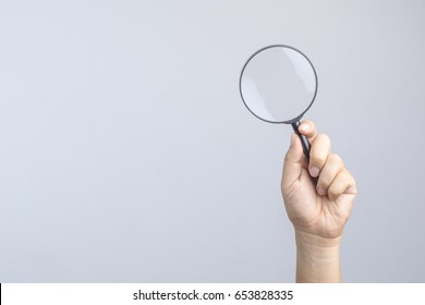 Hand holding magnifier on white background