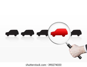 Hand holding magnifier over red picture of car in row of black cars. White background. Concept of choice.