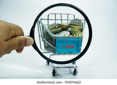 A hand holding a magnifying glass close up with a pile of coins currency of Malaysia  (MYR) in a trolley on isolated white background. A finance, saving and business concept.