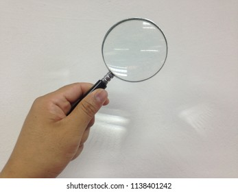 Hand holding magnifying glass isolated on white background.
