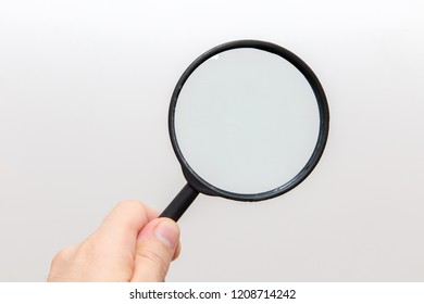 Hand holding magnifying glass on white background