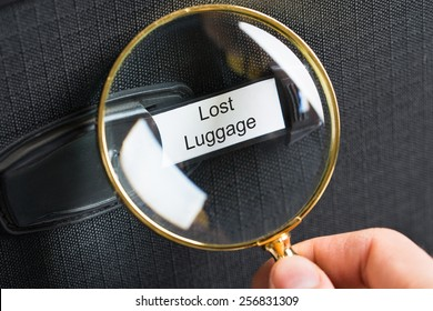 Hand Holding Magnifying Glass On Travel Bag With A Lost Luggage Label