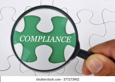"""Hand Holding Magnifying Glass Seaching Missing Puzzle Pieces """"COMPLIANCE"""""""