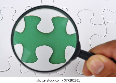 Hand Holding Magnifying Glass Searching Missing Puzzle Pieces