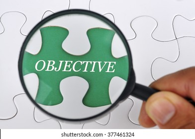 """Hand Holding Magnifying Glass Searching Missing Puzzle Pieces """"OBJECTIVE"""""""