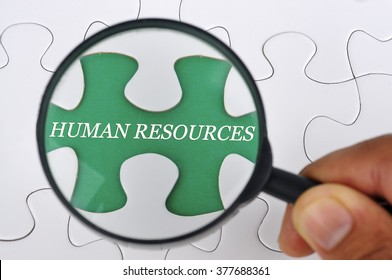 """Hand Holding Magnifying Glass Searching Missing Puzzle Pieces """"HUMAN RESOURCES"""""""