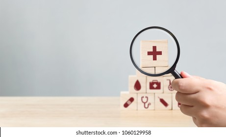 Hand holding magnifying glass to wood block stacking with icon healthcare medical, Insurance for your health concept
