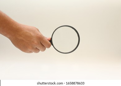 Hand holding a magnifying glasses with isolated background